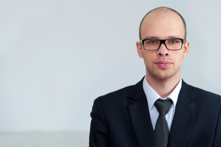 bald man: Retrato de un apuesto hombre de negocios grave, llevaba gafas sobre fondo gris