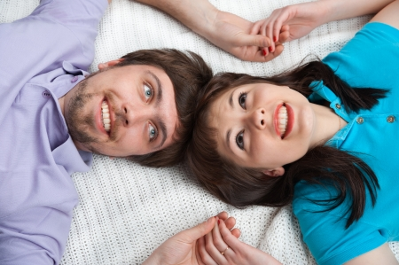Cropped view of a young couple lying in bed and looking up. Man and woman holding hands photo