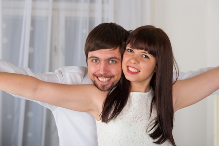 Closeup portrait of a joyful young couple flying against home interior photo