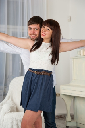Portrait of a joyful young couple flying against home interior photo