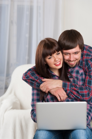Portrait of young smiling couple using laptop while sitting on couch at home. With part for copy space photo