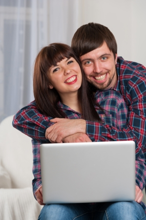 Portrait of young smiling couple using laptop while sitting on couch at home photo