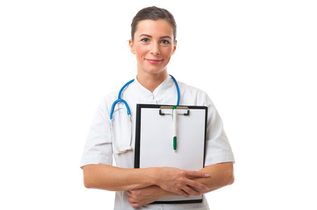 Portrait of caucasian attractive thoughtful smiling doctor female holding clipboard with pen. Isolated shot of doctor woman with brown hair with stethoscope on the neck photo