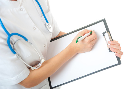Portrait of female doctor with blue stethoscope on neck writing on blank clipboard on white background. Isolated woman doctor in white medical gown photo