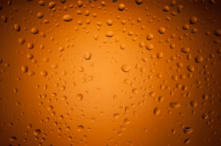suface: Closeup macro view of water drops on orange glass suface Stock Photo