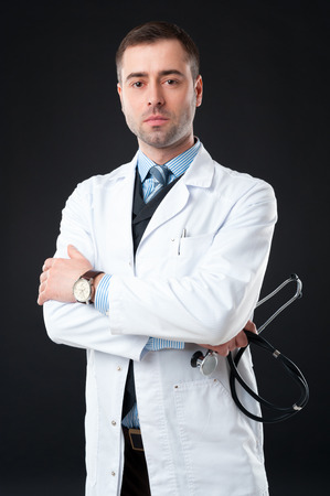 Handsome mature Serious male doctor with stethoscope in hand on black or dark grey background. Classic style in waistcoat with blue shirt and tie photo