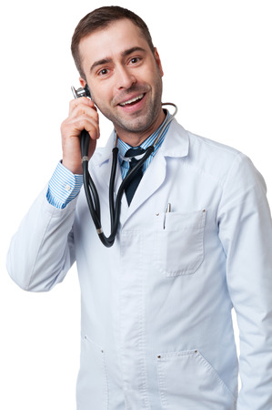Smiling male doctor holds stethoscope in hand as mobile telephone isolated on white background photo