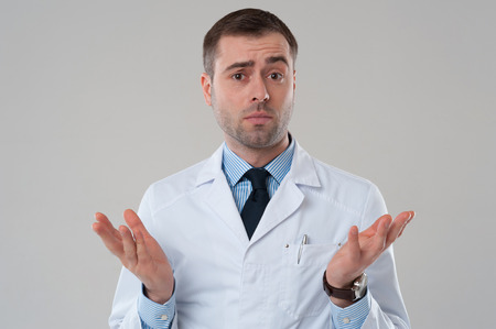 Handsome mature male doctor shrugging lifting shoulders on grey background. Mature doctor man shrug isolated on grey background
