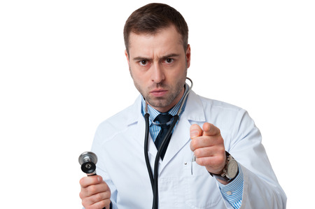 Serious male doctor holds stethoscope in hand and pointing at camera isolated on white background. Stethoscope in ears