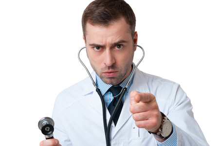 Serious male doctor holds stethoscope in hand and pointing at camera isolated on white background. Stethoscope in ears photo