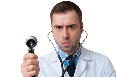 Serious male doctor holds stethoscope in hand isolated on white background. Stethoscope in ears photo