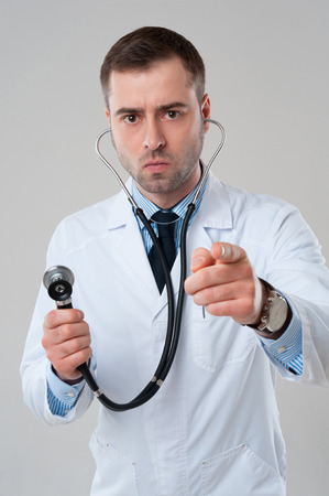 Serious male doctor holds stethoscope in hand and pointing at camera isolated on grey background. Stethoscope in ears photo