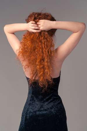 Portrait of young slim beautiful woman in black dress with long red hairs standing on grey background. Woman touch her hairs photo
