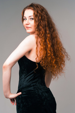 Portrait of young beautiful woman in black dress with long red hairs standing on grey background photo