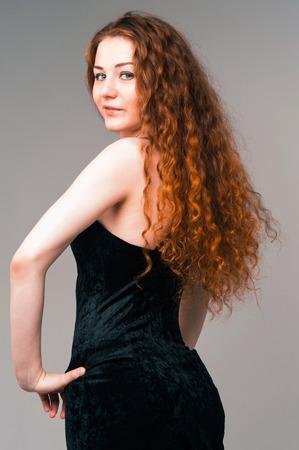Retrato de mujer joven y bella en vestido negro con pelos rojos largos de pie sobre fondo gris photo