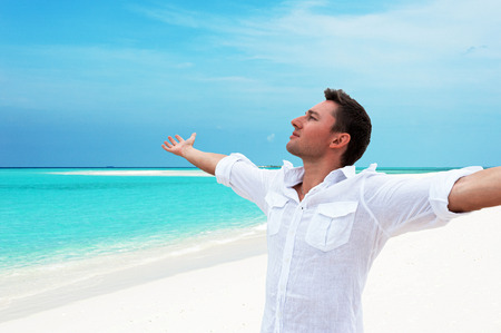 Attractive happy smiling male looking around away into the distance with his raised hands up against beautiful beach with white sand and blue water of indian ocean. Summertime at paradise place at Maldives