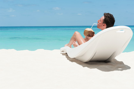 caribbean drink: Man enjoy lying on lounger sunbed and drinking coconut cocktail on beach with white sand and blue indian ocean. Summertime at paradise place at Maldives
