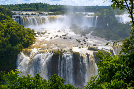 Iguazu Falls or Iguassu Falls in Brazil. Beautiful Cascade of waterfalls with clouds and jungle photo