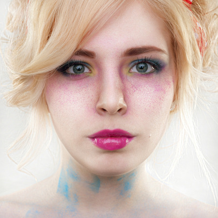 Bright colorful creative make-up on woman face with powder on skin in studio photo
