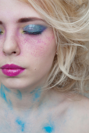 Modern futuristic Bright colorful creative make-up on woman face with powder on skin in studio photo