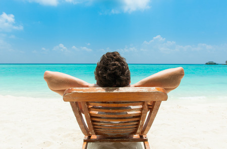 Man relaxing on beach, ocean view, Maldives island Stockfoto