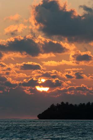 Silhouette de l'île de Palm dans l'océan indien sur le fond de coucher de soleil et nuages