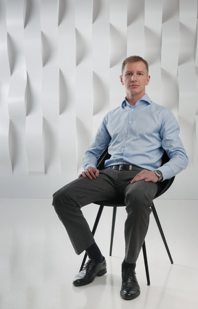 sits on a chair: Business man sits on chair against background of abstract modern urban interior Stock Photo