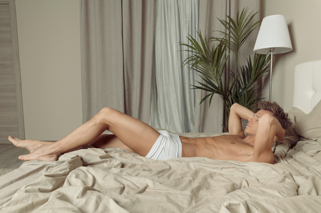 Fit handsome man in underwear relax on bed in bedroom