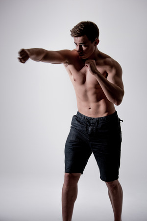 pugilist: Portrait of powerful fighter man in fighting stance. Martial arts.