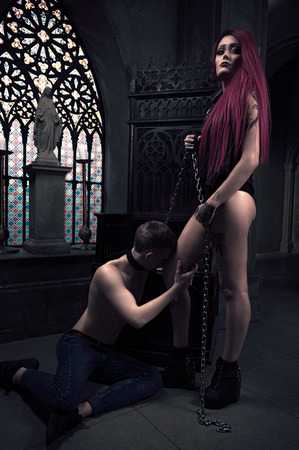 submissive: Girl with tattoos as master and her submissive man in temple