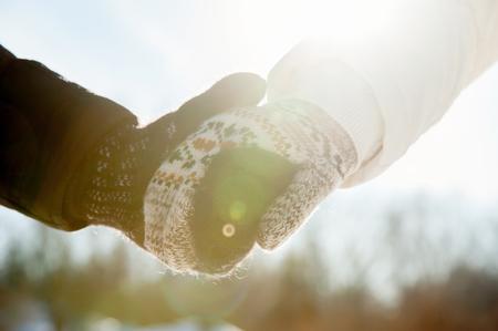 Pár se drží za ruce v rukavicích v zimním období při slunečním světle