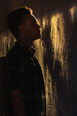 Contrast silhouette of man standing near wall in bright warm sun light at summer sunset