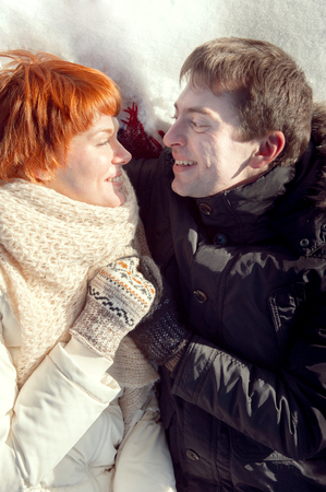 Smiling young couple hug on snow and looking to each other