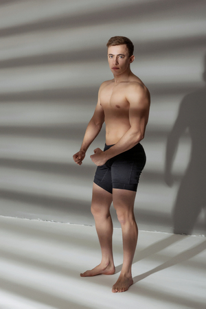 Fit sports man showing his naked torso on grey background