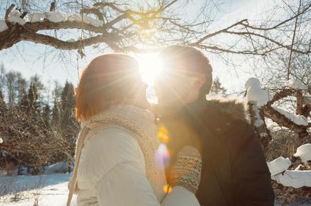Happy kissing couple on winter park background at sunlight Standard-Bild