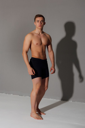 Sports man showing his naked torso on grey background