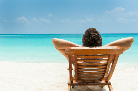 Man relaxing on beach, ocean view, Maldives island Zdjęcie Seryjne