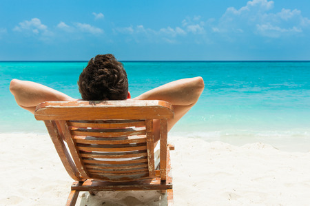 Man relaxing on beach, ocean view, Maldives island Stock Photo