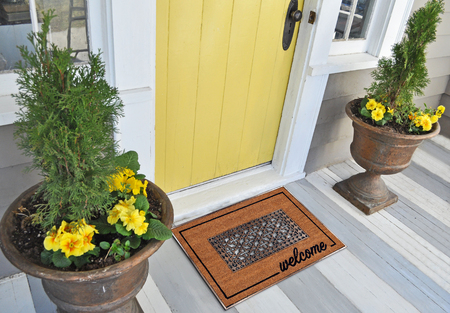 Beautiful Classic beige zute and black rubber border Outdoor Doormat with welcome text outside home with yellow flower pots Imagens