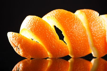 peels: Spiral orange peel reflecting on black background