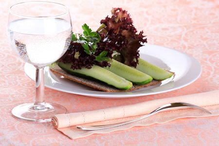 Fresh green salad with glass of water photo
