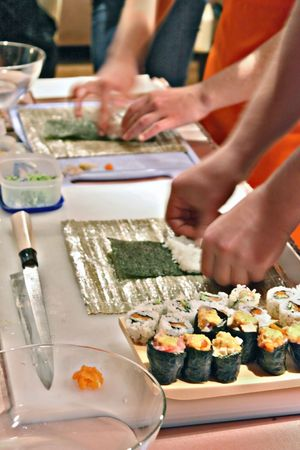 california roll: people  preparing sushi in the  kitchen  Stock Photo
