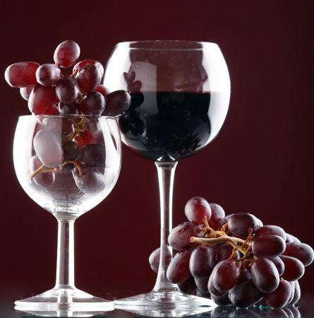 a glass of red wine and grape photo