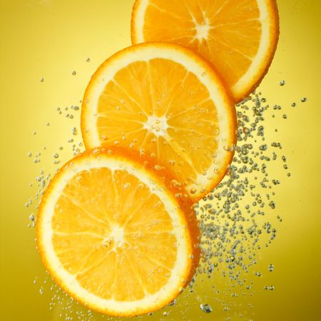 fallin:   Fresh orange dropped into water with bubbles