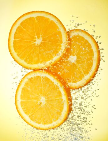 fallin: Fresh orange dropped into water with bubbles  Stock Photo