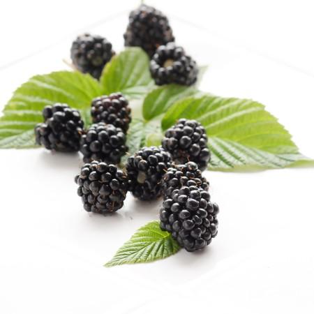 dewberries (blackberries) and green leaves Stock Photo