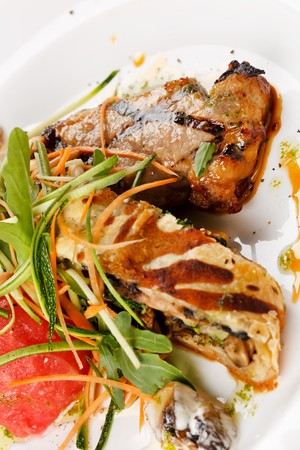 Grilled pork steak with vegetable garnish.  photo
