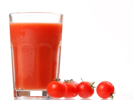 Fresh tomatoes and a glass full of tomato juice  photo