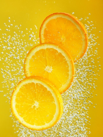 Fresh orange dropped into water photo