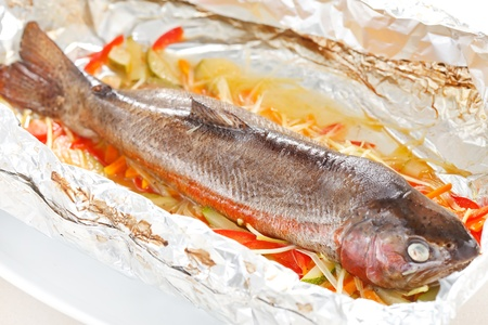 Trout baked with vegetables in the foil photo